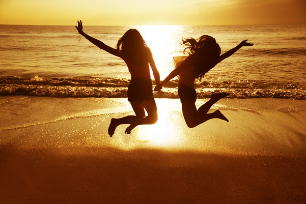 Two girls jumping with beach sunset in background